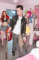 Stylish man holding guitar with two sexy women standing behind