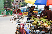 A street vendor selling fresh coconuts as a cycle rickshaw passes in the background on the street in Dhaka, Bangladesh.