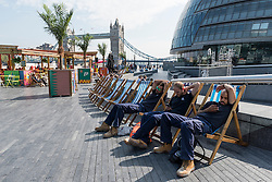 © Licensed to London News Pictures. 14/09/2016. London, UK. Workmen on a break enjoy the hot weather around City Hall as September's mini heatwave continues.  Photo credit : Stephen Chung/LNP