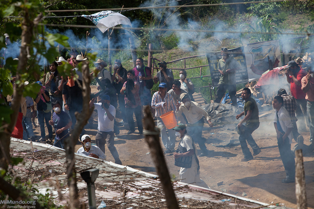 Locals from the La Puya peaceful resistance resist as tear gas canisters are launched by riot police. After two years and two months of peacefully blocking the entrance to U.S.-based Kappes, Cassiday & Associates (KCA) El Tambor gold mine, local residents of San Jose del Golfo and San Pedro Ayampuc were violently evicted by Guatemalan Police forces in order to introduce heavy machinery inside the industrial site. La Puya, San Pedro Ayampuc, Guatemala. May 23, 2014.