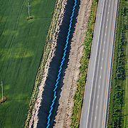 Water pipe is layed along the highway outside of Williston, North Dakota. The demand for water is high with oil and fracking interests in the Bakken formation as well as the exponential population growth. The oil boom is redrawing North Dakota's landscape, however, the economic prosperity has exacerbated problems in housing, infrastructure and traffic. ..Known for the beauty of its great plains, North Dakota has long been the least populated state in the country. Because of the Bakken oil boom, everyday, mostly men, pour in from across the nation looking for work. The small town of Williston has exploded as a result. Ten years ago Williston, North Dakota was a quiet agricultural town with a population around 12,000. In a decade the population has more than doubled to over 30,000. More than half of Williston's residents now work in oil-related jobs and the city's unemployment rate is at 1 percent, which is the lowest in the U.S...