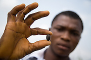 Farm worker Thomas Kavi holds a jatropha seed at the farm where he works in the town of Lolito, roughly 80km east of Ghana's capital Accra, on Thursday Dec. 12, 2006. Jatropha - which grows naturally in Ghana and other parts of Africa - can be used to make biodiesel.<br />
