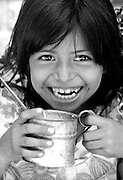 Young girl drinking milk and oatmeal provided to her school by USAID.