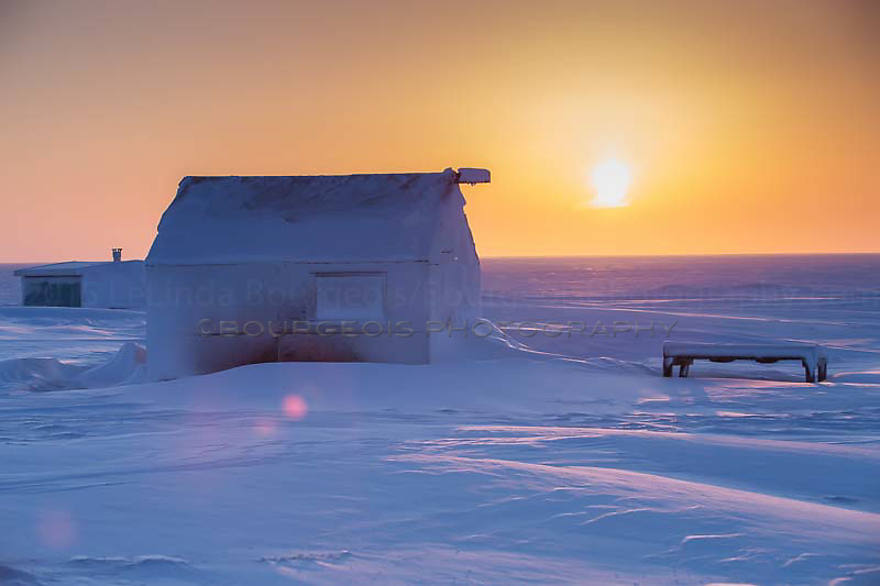 Cabin along the Arctic Ocean at sunset in the middle of winter.