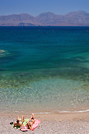 A couple lying on a pebble beach next to the sea outside Agios Nikolaos, Crete, Greece