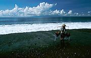 Kusamba, black volcanic beach. Fetching sea water buckets for salt extraction.