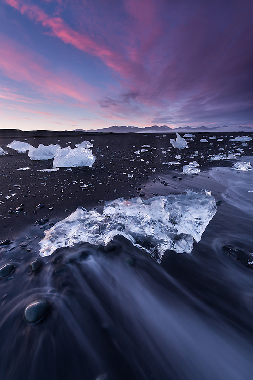 Water pattern caused by outgoing wave creates an interesting foreground shape with stranded icebergs at sunset along the beach at Jokulssrlon, Iceland