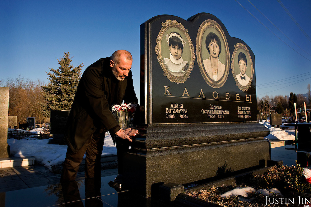Vitali Kaloyev touching the grave of his wife and children in Vladikavkaz, in North Ossetia in southern Russia. .The 52-year-old architect, who killed the air traffic controller blamed for the plane crash in which he lost his wife and two children, is being treated as a national hero..Kaloyev, who was freed November 2007 from a Swiss jail after serving less than four years, was appointed deputy construction minister for his home region..Kaloyev was building a holiday villa in Spain for a wealthy Russian when his wife Svetlana, 44, 10-year-old son Konstantin and four-year-old daughter Diana, set out to join him for a holiday in July 2002. As their plane flew over Germany it collided with a cargo jet killing all 71 people on board, most of them Russian schoolchildren..Investigators later established that Peter Nielsen, a Dane working for Skyguide, the Swiss air-traffic control service at Zurich airport, was the only person on duty. He had panicked when he realised the two planes were on a collision course and gave wrong instructions to the pilots..Like other bereaved relatives, Kaloyev grew angry at the slow pace of the investigation and the way Skyguide, fearful of lawsuits, sought to place the blame on others..Kaloyev claims he cannot remember what happened next, but does not deny stabbing Nielsen several times with a pocket knife. Nielsen bled to death before an ambulance could reach him. Kaloyev was arrested the following day and was sentenced to eight years for manslaughter.
