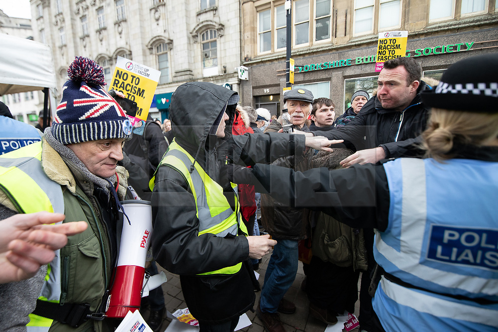 """© Licensed to London News Pictures . 09/02/2019. Manchester , UK . Scuffles break out as anti-fascists block a """" Yellow Vest """" protest on Market Street in Manchester City Centre . The yellow vest concept has been adopted from French demonstrators by some British groups in support of Brexit , Donald Trump and former EDL leader Stephen Yaxley-Lennon - aka Tommy Robinson . A similar demonstration in the city in January was ridiculed after protesters were kettled by police in front of a branch of Greggs the Baker . Photo credit : Joel Goodman/LNP"""