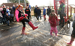 © Licensed to London News Pictures. 02/02/2014. Burrowbridge, UK People play in floodwater. Burrowbridge on the Somerset levels today. The River Parrett broke its banks again at 9.15 am today 2nd February 2014. Photo credit : Jason Bryant/LNP