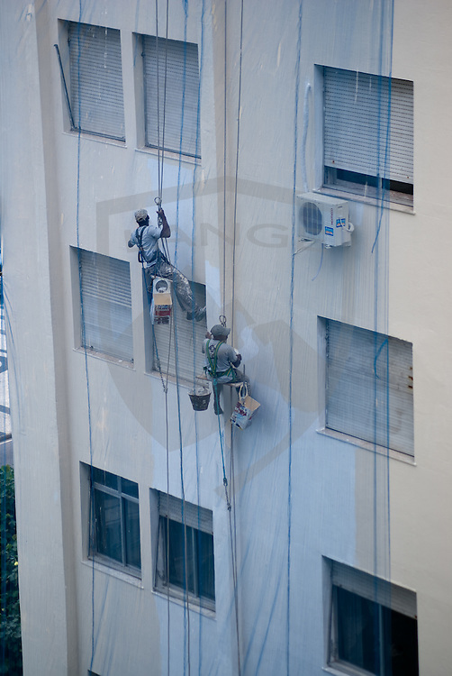 men suspended on side of apartment building painting in copacabana, rio de janeiro, brazil.  preparations for hosting the 2016 olympics are apparent throughout rio de janeiro as urban refurbishing begins in the city.