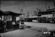 Couple watches trucks from the port go by on Radial Road 10 from beside their makeshift home in the heart of Tondo District, Manila, Philippines.<br /> While the extreme poverty rate in the region dropped significantly between 2005 and 2008, the Philippines' poverty rate remained largely unchanged.  In fact, poverty has intensified on the poor.  According to the National Statistics Coordination Board (NSCB) in 2006, 28.8% of families lived on less than US$1.25/ day.  By 2012, 27.9 % of Filipinos were living below the poverty line.  <br /> <br /> What what changed was the income per family needed to escape extreme poverty.  While in 2006, a family would need to earn US$39.09 / month to escape extreme poverty, that figure rose in the most recent NSCB survey to US$ 181.89/month, clear showing how inflation is weighing heaviest upon that society's poor.