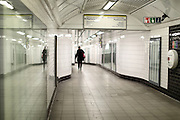 A woman walking towards the District Line at Notting Hill Gate station