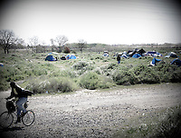 """Robert Burgins rides his bike at a homeless encampment or """"tent city"""" on the banks of the American River in Sacramento, CA."""