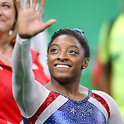 Gymnastics - Olympics: Day 6 Simone Biles #391 of the United States salutes the crowd after winning the gold medal watched by her coach Aimee Boorman during the Artistic Gymnastics Women's Individual All-Around Final at the Rio Olympic Arena on August 11, 2016 in Rio de Janeiro, Brazil. (Photo by Tim Clayton/Corbis via Getty Images)