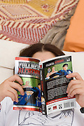 Young female teen of thirteen reading a book of Japanese Manga comics model released