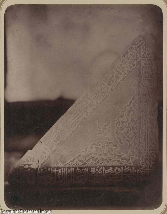 1868<br /> This photograph of a posterior triangular side of the marble Qur'an holder at the main mosque of the Bibi Khanym ensemble in Samarkand (Uzbekistan) is from the archeological part of Turkestan Album. The six-volume photographic survey was produced in 1871-72 under the patronage of General Konstantin P. von Kaufman, the first governor-general (1867-82) of Turkestan, as the Russian Empire&rsquo;s Central Asian territories were called. The album devotes special attention to Samarkand&rsquo;s Islamic architecture, such as 14th- and 15th-century monuments from the reign of Timur (Tamerlane) and his successors. Built in 1399-1405 with the spoils of Timur&rsquo;s campaign in India, the Bibi Khanym ensemble was the location of the city&rsquo;s main, or Friday, mosque, named in homage to Timur&rsquo;s senior wife, Sarai Mulk Khanym. The ensemble centers on the mosque, one of the largest in the Islamic world. Inside the mosque was an enormous Qur'an holder (rihal) donated by Timur&rsquo;s grandson Ulugh Beg and consisting of two massive triangular marble blocks resting on a marble plinth. Shown here is the posterior triangular side of the left block, with carved decoration consisting of floral patterns and bands of cursive script. (Background detail was reduced to highlight the carving.) In 1875, a few years after this photograph, the lectern was moved into the courtyard in front of the mosque.