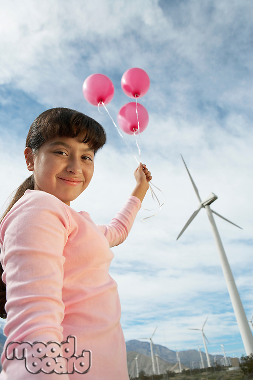 Girl (7-9) holding balloons at wind farm, portrait