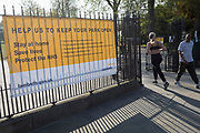 As the UK government's lockdown restrictions during the Coronavirus pandemic continues, and number of UK reported cases rose to 138,078 with a total now of 18,738 deaths, two Londoners pass a banner by Lambeth Council advising on social distancing restrictions and overall behaviour has been stretched across the gates of Brockwell Park, a public green space in the south London borough of Lambeth, on 23rd April 2020, in London, England.