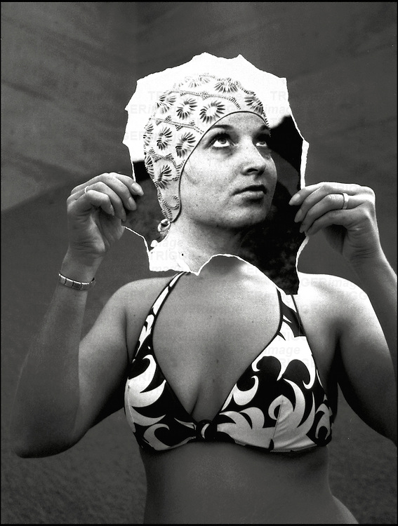 A young woman wearing a bikini holding a photographed head