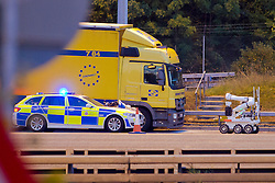© Licensed to London News Pictures. 05/09/2012. London, UK . A bomb disposal robot attends to a suspicious device on the front of a police car that closed the M25 motorway Dartford Bridge and Tolls in both directions on 6th September 2013. One man arrested and a suspicious item found resulting in traffic tailbacks for 7 hours.. Photo credit : Shaun Petri/LNP