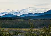 Mount Wrangell, seen from the Edgerton Highway, Alaska, USA. Wrangell-St. Elias National Park and Preserve (the largest National Park in the USA) is honored by UNESCO as part of an International Biosphere Reserve and UNESCO World Heritage Site. Mount Wrangell (14,163 feet) is the largest andesite shield volcano in North America, the park's only active volcano, releasing occasional steam plumes. Shield volcanoes have more frequent, but less violent eruptions than other types. Flowing northward from the great ice fields of Mount Wrangell, the Copper Glacier melts into the Copper River which flows northward, then westward along the end of the Wrangell Range, then southward to the Gulf of Alaska near Cordova, cutting through the coastal barrier of the Chugach Mountains, and marking most of the Parks western boundary.