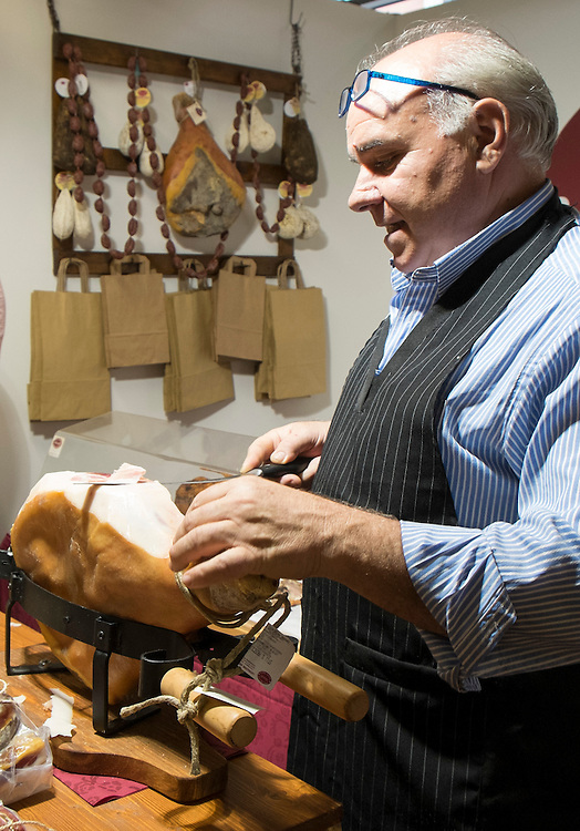 Mr Morelli, a traditional  Norcinaio slices a ham at his stand of the Biennale del Gusto on October 28, 2013 in Venice, Italy. The Biennale del Gusto is an exhibition held over four days, dedicated to traditional food and drinks from all regions of Italy.