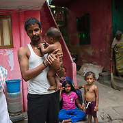 A family poses for a photograph in a slum in Saidapet, Chennai, India.