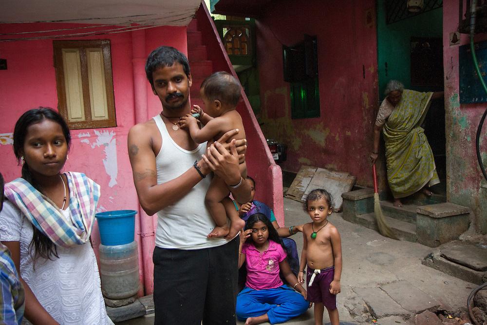 A family poses for a photograph in a slum in Saidapet, Chennai, India.