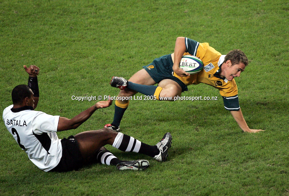 Australia's Kiernen Masseysteps out of the tackle of Apolosi Sataqla during their pool match at the 2005 Rugby World Cup Sevens, Hong Kong, Saturday 19 March 2005. Fiji defeated Australia 31-5.<br />PHOTO: Andrew Cornaga/PHOTOSPORT