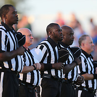 Referee Collins Golden, center and other members refereeing crew listen to the National Anthem before the game between Amory and Saltillo on Thursday.