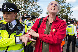 London, UK. 3 September, 2019. Police officers arrest Quakers blocking one of the two main access roads to ExCel London on the second day of week-long protests against DSEI, the world's largest arms fair. Protests were themed around faith and prayer and involved believers deriving from multiple faiths including the Quakers standing in solidarity against arms sales.