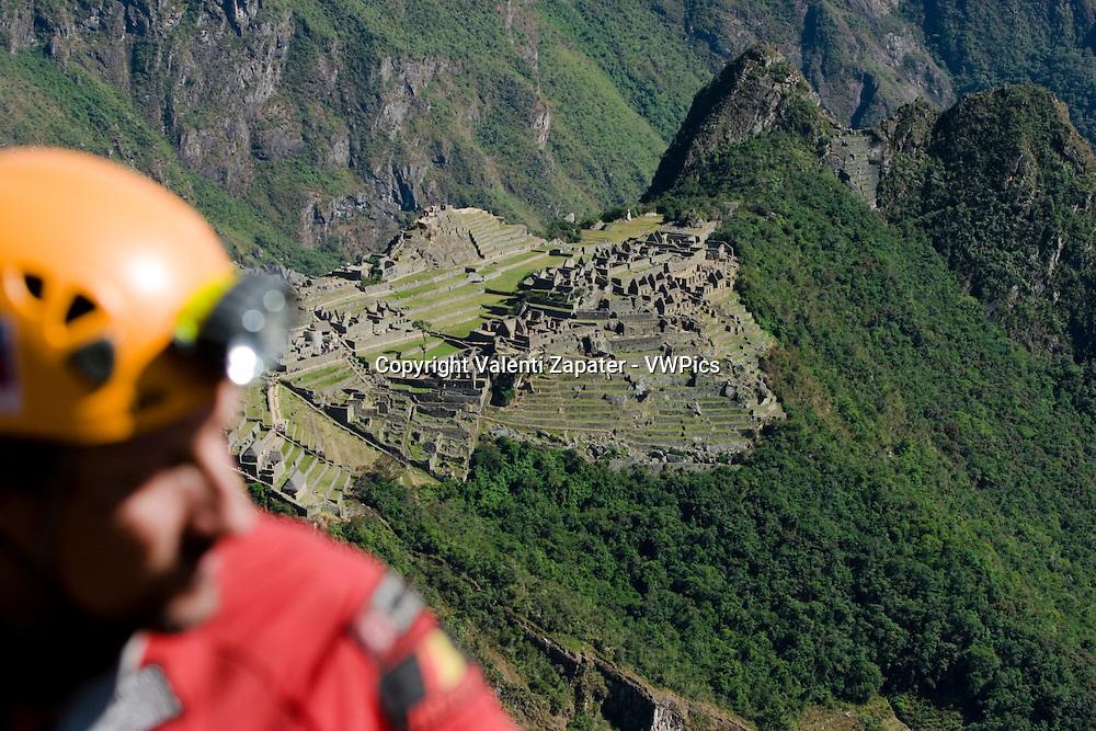 Machu Picchu. In the foreground a caver out of focus. Cusco, Peru. Felipe Sacristán, del Proyecto Ukhupacha, descendiendo una pared en Machupicchu en busca de nuevos caminos incas. Al fondo, la ciudadela prehispánica.