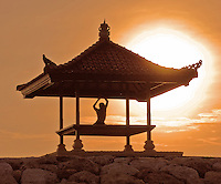 Silhouette of a man practicing yoga in a sunrise-hori in Bali, Indonesia.