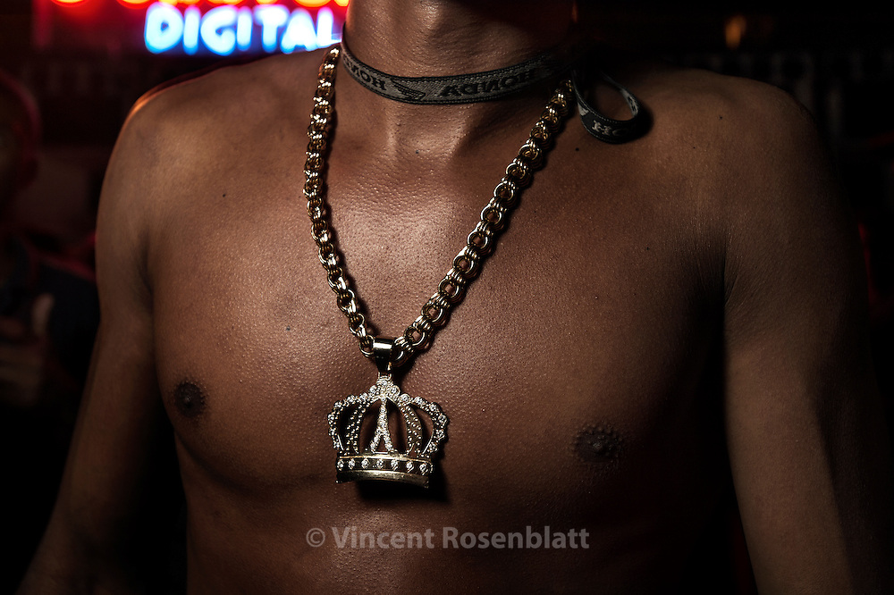 Crown pendant  - Baile Funk in Favela of Reta Velha. Itaboraí, Rio de Janeiro state 2013. The Funk carioca movement is fashion and look as well  : The boys show off their muscles and naked torsos, adorned with chains and tattoos, accessories which will make the difference during the ball.  Girls will look after their bikini marks, which will appear above mini-skirts or micro-shorts.  Everything is worth to draw attention! .