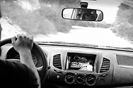 Rebel fighter drives to an outpost along Dafniya front line, west of Misrata, with a grenade at hand reach on the dashboard. 23 May 2011.