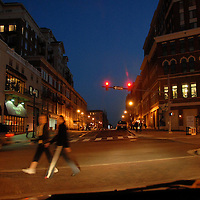 Pedestrians cross an intersection in the Clarendon neighborhood of Arlington, Virginia illuminated by headlights in the evening.