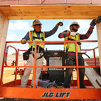 Cristobal Brianes and Juan Beltran, employees with Dome Technology in Idaho Falls Idaho, install frame work on all the openings on the new gymnasium being built at Tupelo High School on Wednesday morning. The openings must be air tight for the roof to be inflated during its installation.