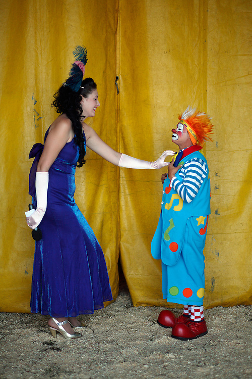 The Mistress of Ceremonies helps a clown prepare backstage behind curtains at the Cole Brother Circus in Wilmington, North Carolina.
