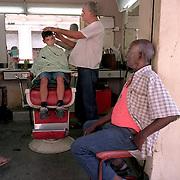 """The children of Havana."" A Cuban boy gets his hair cut in an open-air barbershop in Havana Vieja."