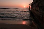 The sun sets on the horizon along side the Kapahulu Groin in Waikiki.