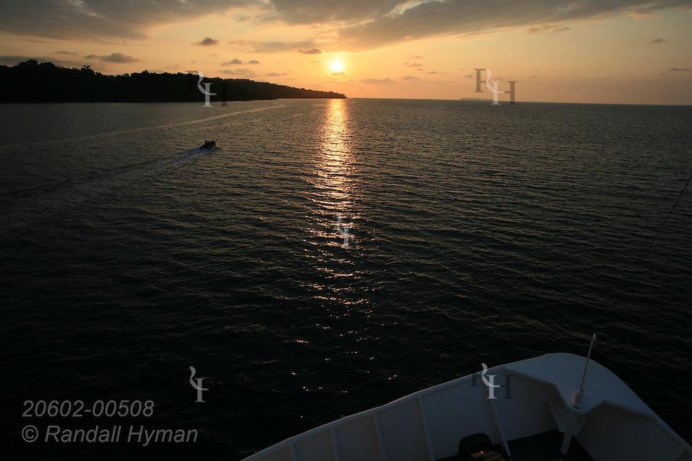 Zodiac speeds across Drake Bay toward horizon as bow of small cruise ship frames sunset over Pacific Ocean's Osa Peninsula at Corcovado National Park, Costa Rica.