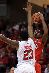 29 November 2014:  Shawn Amiker takes a shot with Deontae Hawkins in his face during an NCAA men's basketball game between the Youngstown State Penguins and the Illinois State Redbirds  in Redbird Arena, Normal IL.