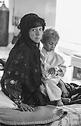 IRAQ, BAGHDAD:  Young Iraqi Muslim mother in the hospital with her son who is suffering from malnutrition and dehydration during the UN Sanctions against Iran.   He is being treated with glucose at the Sadaam Hussein Children's Teaching Hospital in Baghdad.  Grainy black and white historical  print.