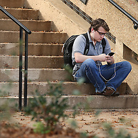 Adam Robison | BUY AT PHOTOS.DJOURNAL.COM<br /> Ole Miss student Skip Keyton, a sophomore from Fort Smith Arkansas, sits outside Lamar Hall scrolling through his phone Thursday afternoon in Oxford.
