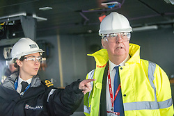 United Kingdom Secretary of State for Defence Michael Fallon with Lt Rachel Campbell, deputy navigator, on the bridge, during a tour of the Queen Elizabeth Aircraft Carrier, which is under construction at the Babcock site in Rosyth dockyard.