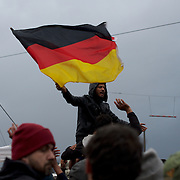 A refugee is seen waiving a German flag during a demonstration at the Greek-Macedonian border near the Greek village of Idomeni. Around 13,000 migrants and refugees, mostly from the Middle East and African nations, are believe to be stranded here awaiting a chance to proceed their journey towards Germany and other northern European countries.
