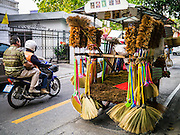 "05 MARCH 2013 - BANGKOK, THAILAND:  A broom vendor pushes his cart past a motorcycle taxi in an upscale neighborhood in Bangkok. Thailand's economic expansion since the 1970 has dramatically reduced both the amount of poverty and the severity of poverty in Thailand. At the same time, the gap between the very rich in Thailand and the very poor has grown so that income disparity is greater now than it was in 1970. Thailand scores .42 on the ""Ginni Index"" which measures income disparity on a scale of 0 (perfect income equality) to 1 (absolute inequality in which one person owns everything). Sweden has the best Ginni score (.23), Thailand's score is slightly better than the US score of .45.  PHOTO BY JACK KURTZ"