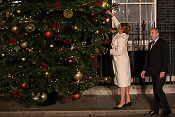 London, UK. 3 December, 2019. Desislava Radeva, wife of Bulgarian President Rumen Radev, hangs a decoration on the Downing Street Christmas tree as she arrives with her husband for a reception for NATO leaders on the eve of the military alliance's 70th anniversary summit at a luxury hotel near Watford.