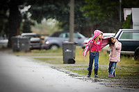 JEROME A. POLLOS/Press..Sarah Timmons, 8, tries to keep her sister, Rachel Timmons, 6, sheltered from the rain Monday on their way home in Coeur d'Alene.